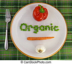 "A white plate with ""Organic"" spelled out in vegetables on a..."
