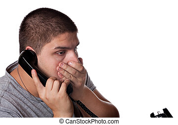 Upsetting Phone Call - A young man on the phone places his...