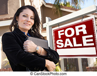 Proud, Attractive Hispanic Female Agent In Front of For Sale Real Estate Sign and House.