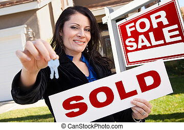 Happy Attractive Hispanic Woman Holding Sold Real Estate...