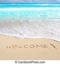greetings welcome beach spell written on sand Caribbean...
