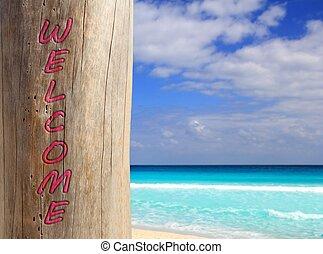 Caribbean beach spell welcome written in pole