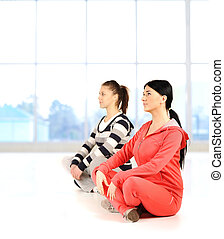 Two girls doing yoga and fitness  in bautiful bright surround