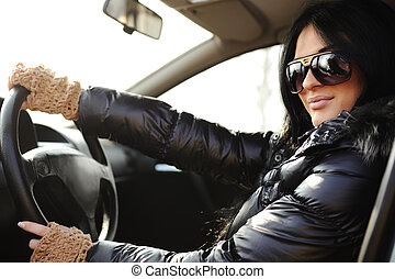 Young beautiful brunette inside the car with wheel in hands