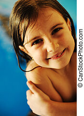 Little cute girl in pool smiling, grainy photo