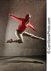young female dancing on the grey wall background