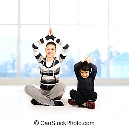 Family - young woman and kid - doing yoga exercises indoors