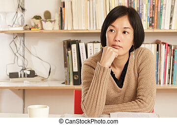 Woman sitting and thinking at home with copyspace