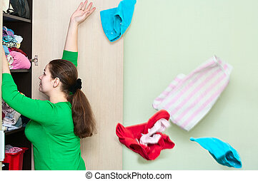 Young caucasian woman throwing a clothes from the wardrobe...