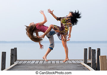 two girl  are dancing on background of water and sky