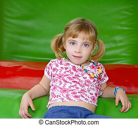 blond little girl resting on colorful playground
