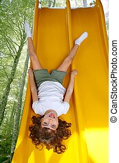 Brunette little girl upside down playground slide forest...