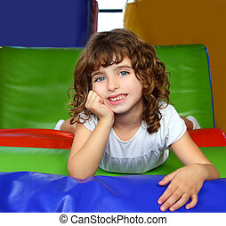 brunette little girl portrait posing in playground colorful