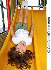 upside down little girl on playground slide laughing happy...