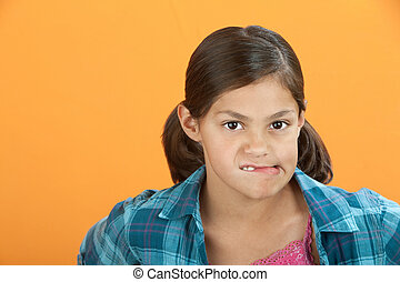 Worried Little Girl - Latina girl on orange background bites...