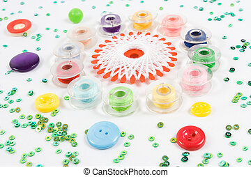 multicolor bobbins, buttons and beads on white background -...