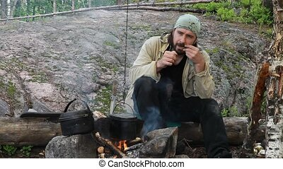 Thoughtful man play on Jew's harp (Khomus) at bonfire in...