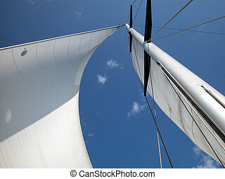 White sail against blue sky - A view looking upwards at the...