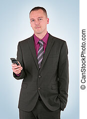 Young businessman using a smart phone, isolated on blue