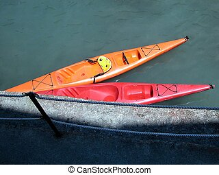Two canoes - Orange and red canoes on blue sea
