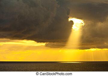 sunbeam and ocean - single sunbeam shining through dark...