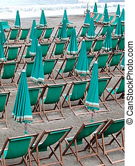 Deckchairs and umbrellas - Series of green deckchairs and...
