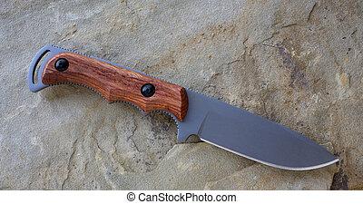 knife - wood handled knife on a single rock