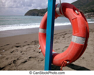 Red lifebelt on the beach - View of a red lifebelt with...