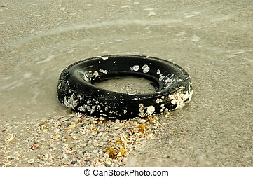 Sea Tire - Old tire covered with shels laying in ocean surf