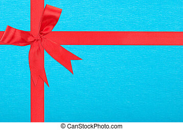 Red satin ribbon and bow gift box wrapping over blue paper background