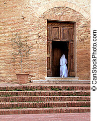 Nun enter in the church - White dressed nun going to the...