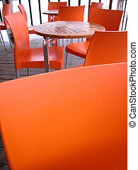 Outdoor cafe - Orange plastic chairs and wood tables in an...
