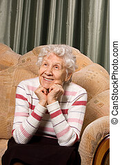 Portrait of the old woman on a sofa