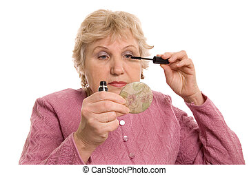 The elderly woman does a make-up