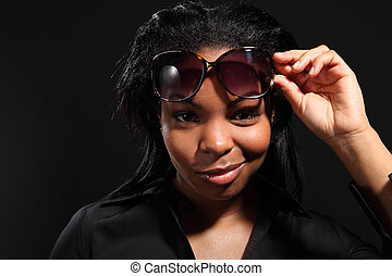 Fun smile by young woman wearing sunglasses