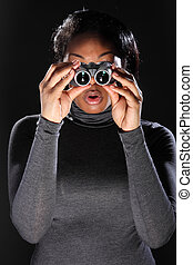 Young woman surprised while using binoculars - I spy. A...