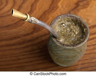 Yerba mate in wooden cup with bombila