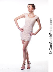 Attractive woman in elegant dress posing on white