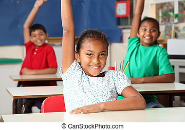 School children arm raised in class - Three happy young...