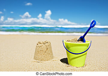 Toy bucket and shovel on the beach on a sunny day