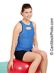 young woman resting on exercise bal - isolated young woman...