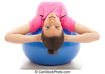 Sit Up - a young girl doing a sit up on a blue exercise ball