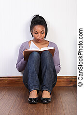 Beautiful woman sitting on floor reading a book