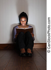 Girl reading horror story book looking frightened -...