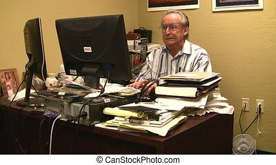 Over Worked - Stressed out man at computer with messy desk