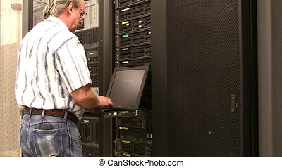 Engineer at data center console - Senior engineer working on...