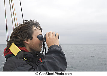 Sailor looking in binoculars - Young sailor looking in...