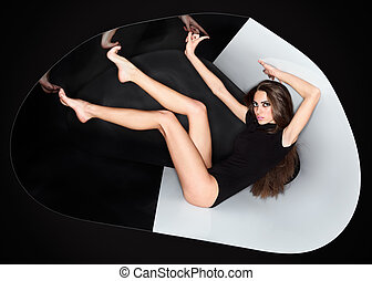 Young slim beautiful lady dressed in black slinky combi dress in abstract plastic tube, ring flash fashion portrait