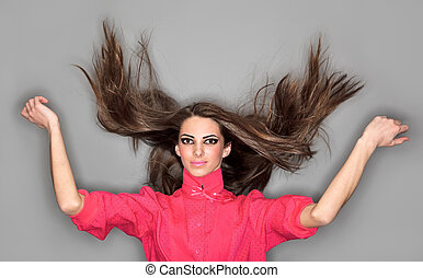 Young cute woman with long hairs flying upwards dressed in pink blouse, ring flash studio portrait on gray