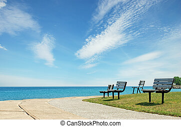 row of park bench with blue sky and clouds